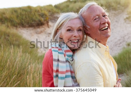 Portrait Of Senior Couple Standing By Sand Dunes - stock photo