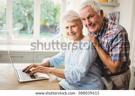 Portrait of senior couple using laptop at homeq - stock photo