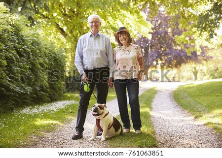 Portrait Of Senior Couple Walking Pet Bulldog In Countryside