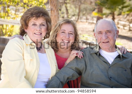 Portrait of Senior Couple with Daughter in the Park. - stock photo