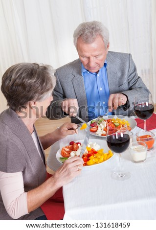 Portrait Of Senior Couple With Wine Glasses Sitting At A Restaurant