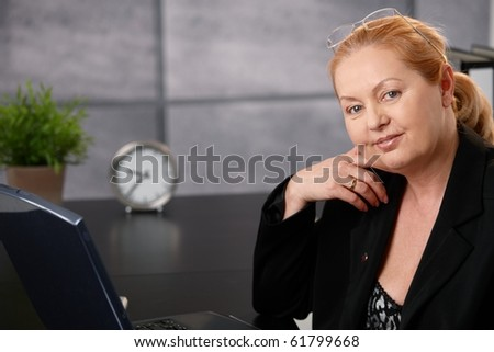 Portrait of senior executive businesswoman sitting at desk in office, looking at camera. - stock photo