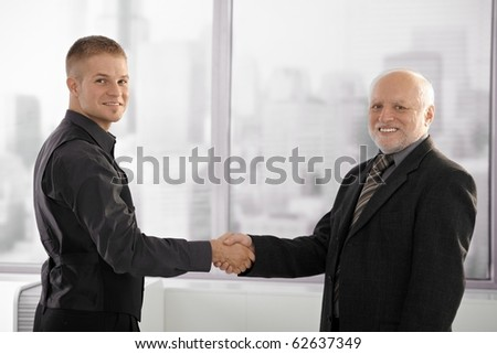Portrait of senior executive shaking hands with young employee, looking at camera, smiling.? - stock photo