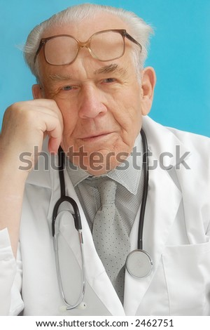 Portrait of senior family doctor with stethoscope - stock photo