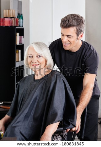 Portrait of senior female client with hairstylist standing behind at salon - stock photo