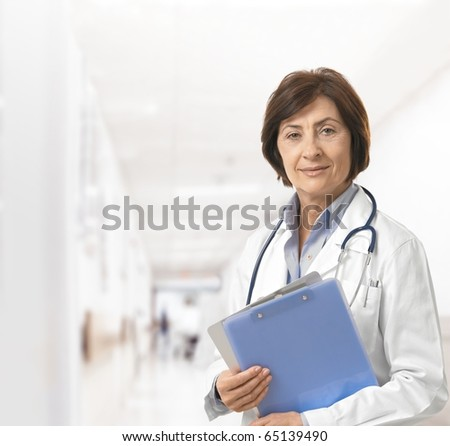 Portrait of senior female doctor on hospital corridor holding clipboard looking at camera smiling.? - stock photo