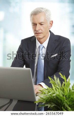 Portrait of senior female doctor standing at hospital while hands in her pockets.  - stock photo