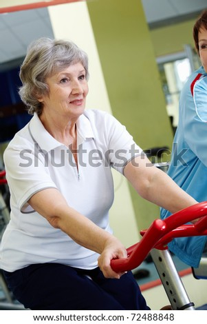 Portrait of senior female doing physical exercise on special equipment - stock photo