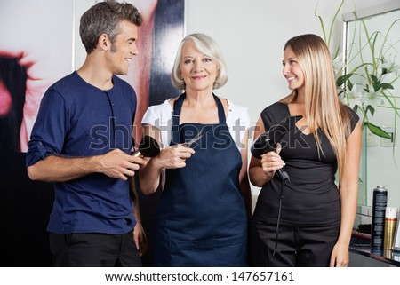 Portrait of senior female hairdresser holding scissors while colleagues with brush and dryer in salon - stock photo