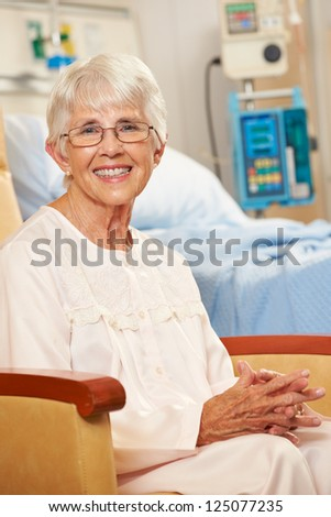 Portrait Of Senior Female Patient Seated In Chair By Hospital Bed - stock photo