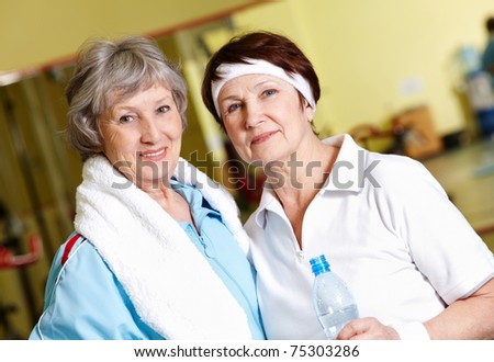 Portrait of senior females looking at camera in gym - stock photo