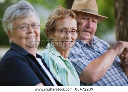 Portrait of senior friends sitting together in park - stock photo