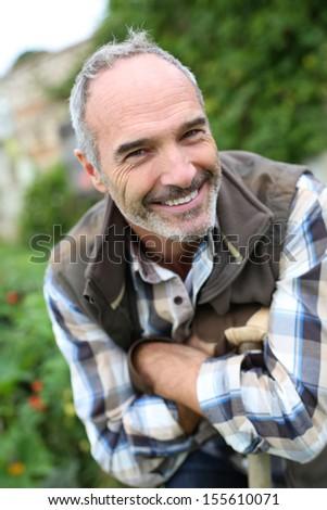 Portrait of senior gardener in vegetable garden - stock photo