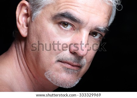 Portrait of Senior Handsome Man looking thoughtfully at the camera, on black background - stock photo