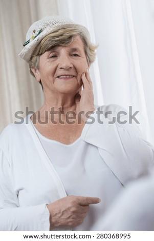 Portrait of senior happy stylish lady in white clothes - stock photo