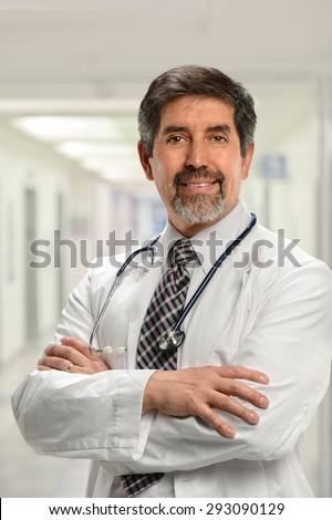 Portrait of senior Hispanic doctor with arms crossed inside hospital building - stock photo