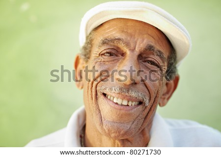portrait of senior hispanic man with white hat looking at camera against green wall and smiling. Horizontal shape, copy space - stock photo