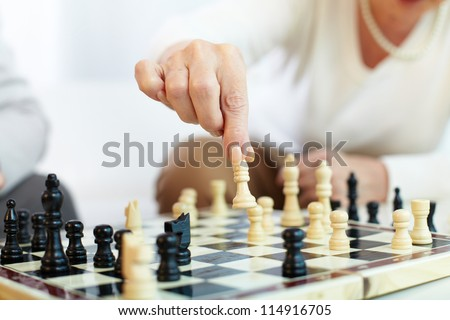 Portrait of senior human hand holding chess figure - stock photo