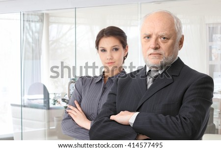 Portrait of senior male boss and young female secretary standing arms crossed.