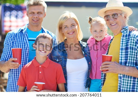 Portrait of senior man and young couple with their children looking at camera outdoors - stock photo