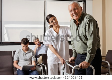 Portrait of senior man being assisted by female nurse to walk Zimmer frame with people sitting in background - stock photo