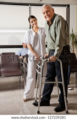 Portrait of senior man being assisted by female nurse to walk Zimmer frame with person sitting in background - stock photo