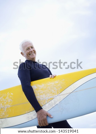 Portrait of senior man carrying surfboard against sky - stock photo