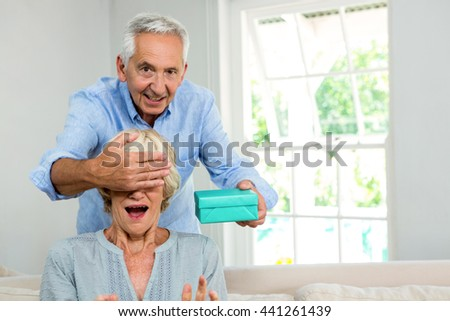 Portrait of senior man covering woman eyes to give surprise at home - stock photo