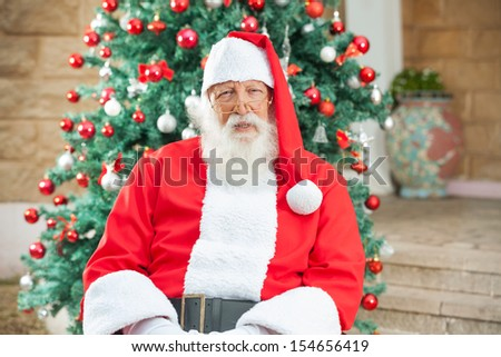 Portrait of senior man dressed as Santa Claus sitting against Christmas tree - stock photo
