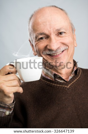 Portrait of senior man drinking cup of coffee on a gray background