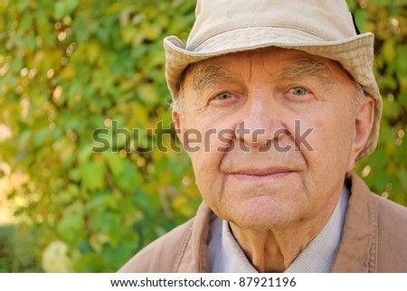 portrait of senior man in his garden - stock photo