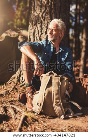Portrait of senior man looking away while sitting by a tree. Senior man with a backpack outdoors on a summer day. - stock photo