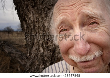 Portrait of senior man outdoors in front of tree