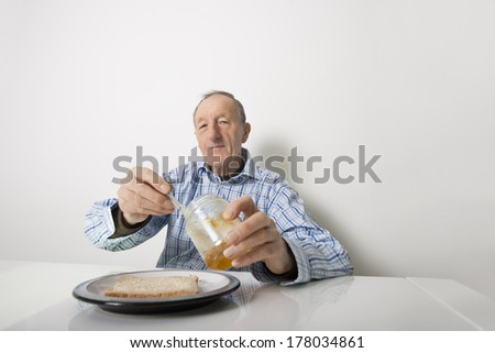 Portrait of senior man preparing slice of bread and marmalade at table - stock photo