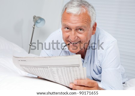 Portrait of senior man reading newspaper lying on bed at home - stock photo