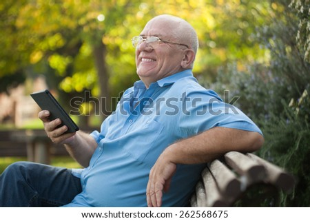 Portrait of senior  man   reading on   bench during autumn day. - stock photo