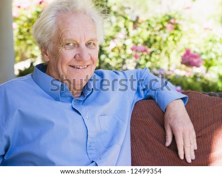 Portrait of senior man relaxing at home sitting on garden seat - stock photo