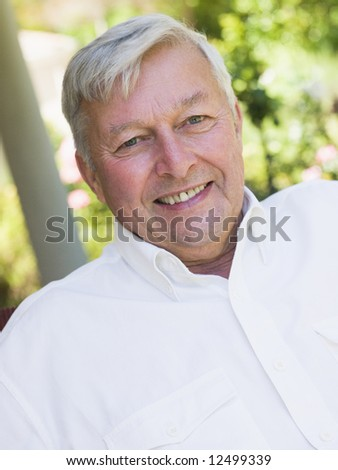 Portrait of senior man relaxing on garden seat - stock photo