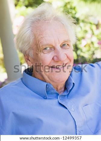 Portrait of senior man relaxing outside on garden seat - stock photo