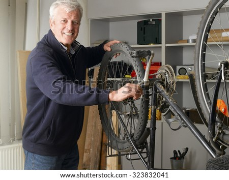 Portrait of senior man repairing bike while standing at his bike shop. Small business.