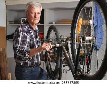 Portrait of senior man repairing bike while standing in his workshop. Small business.