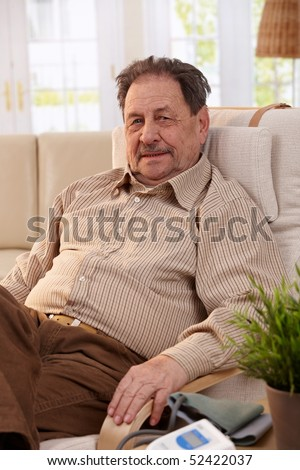 Portrait of senior man resting in armchair, looking at camera.