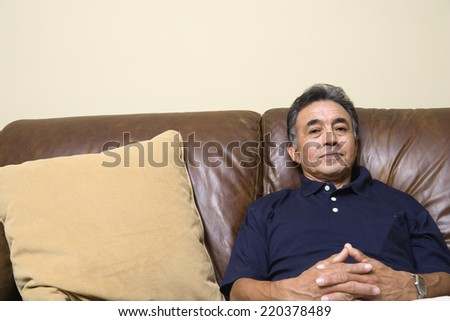Portrait of senior man sitting on couch - stock photo