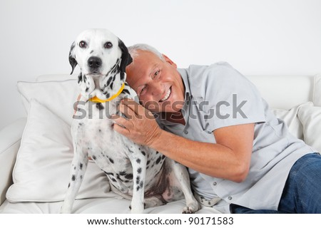 Portrait of senior man sitting on sofa with his pet dog at home - stock photo