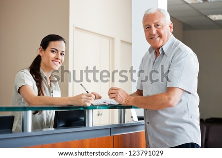 Portrait of senior man standing at hospital reception while female making an entry in book