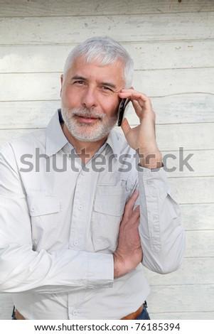 Portrait of senior man talking on the phone - stock photo