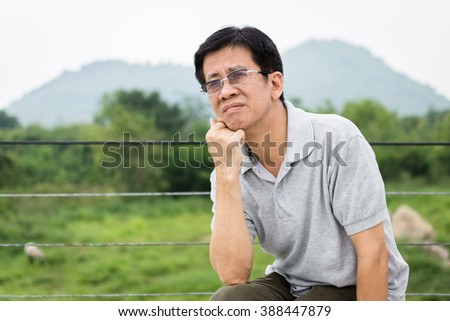 Portrait of senior man thinking about something outdoor mountain nature asia - stock photo