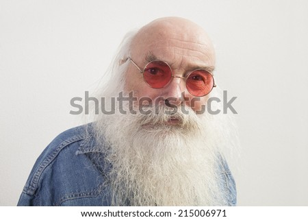 Portrait of senior man wearing red glasses over gray background