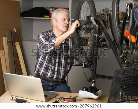 Portrait of senior mechanic worker sitting in his workshop and repairing bike. Small business. - stock photo