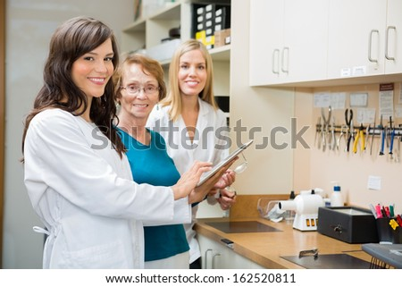 Portrait of senior optician with apprentices using digital tablet in workshop - stock photo